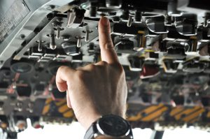 finger of a pilot pushing buttons in an airplane cockpit
