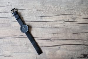 Minimal black watch on artificial wood background